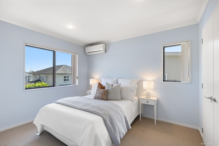 modern bedroom with grey and orange bedding and light blue walls