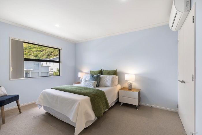 modern bedroom with blue and green bedding and light blue walls