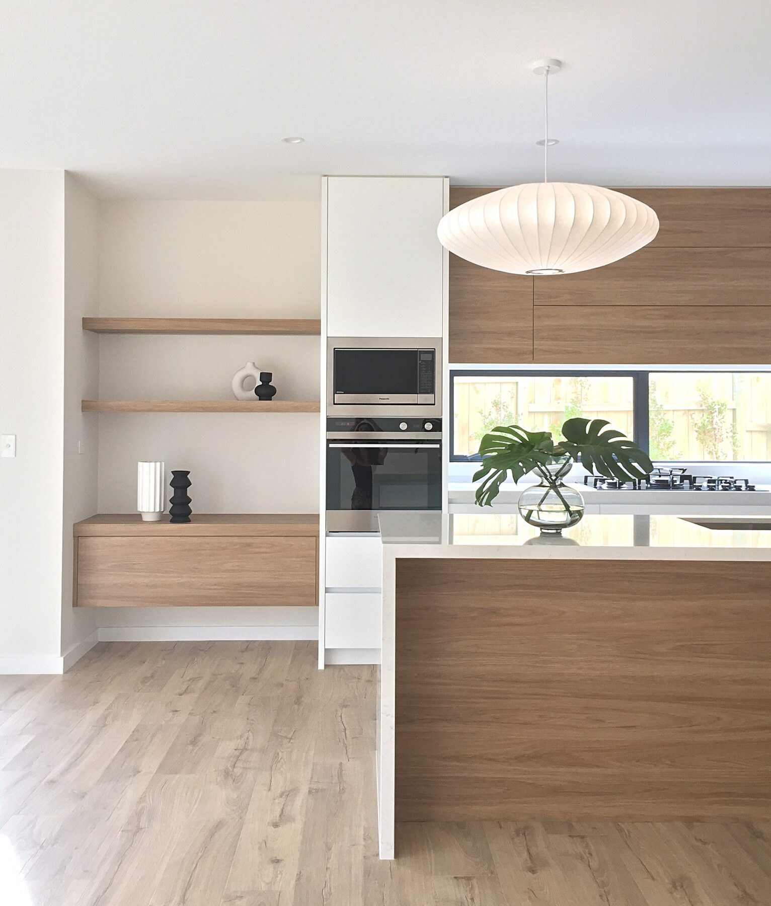 modern kitchen design with stone tops and wooden detailing with built in shelves, simple designer styling, white feature pendant light, plant
