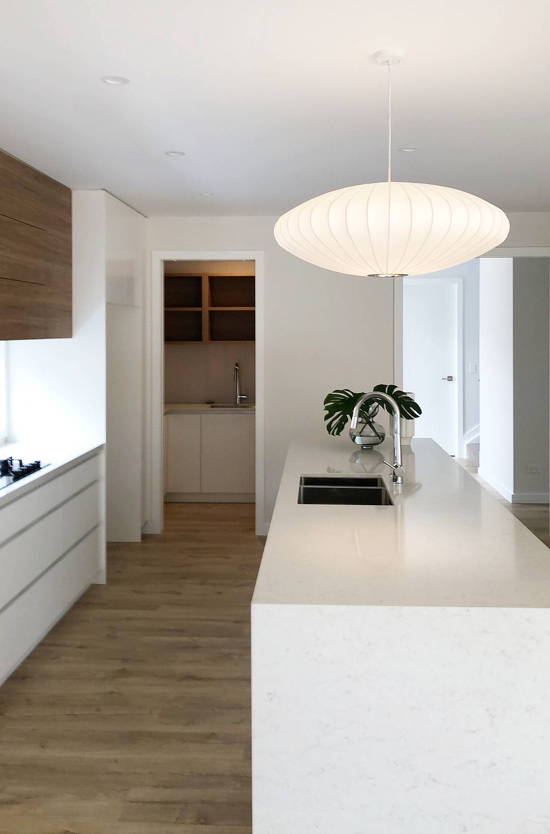 modern kitchen design with stone tops and wooden detailing with built in shelves, white feature pendant light