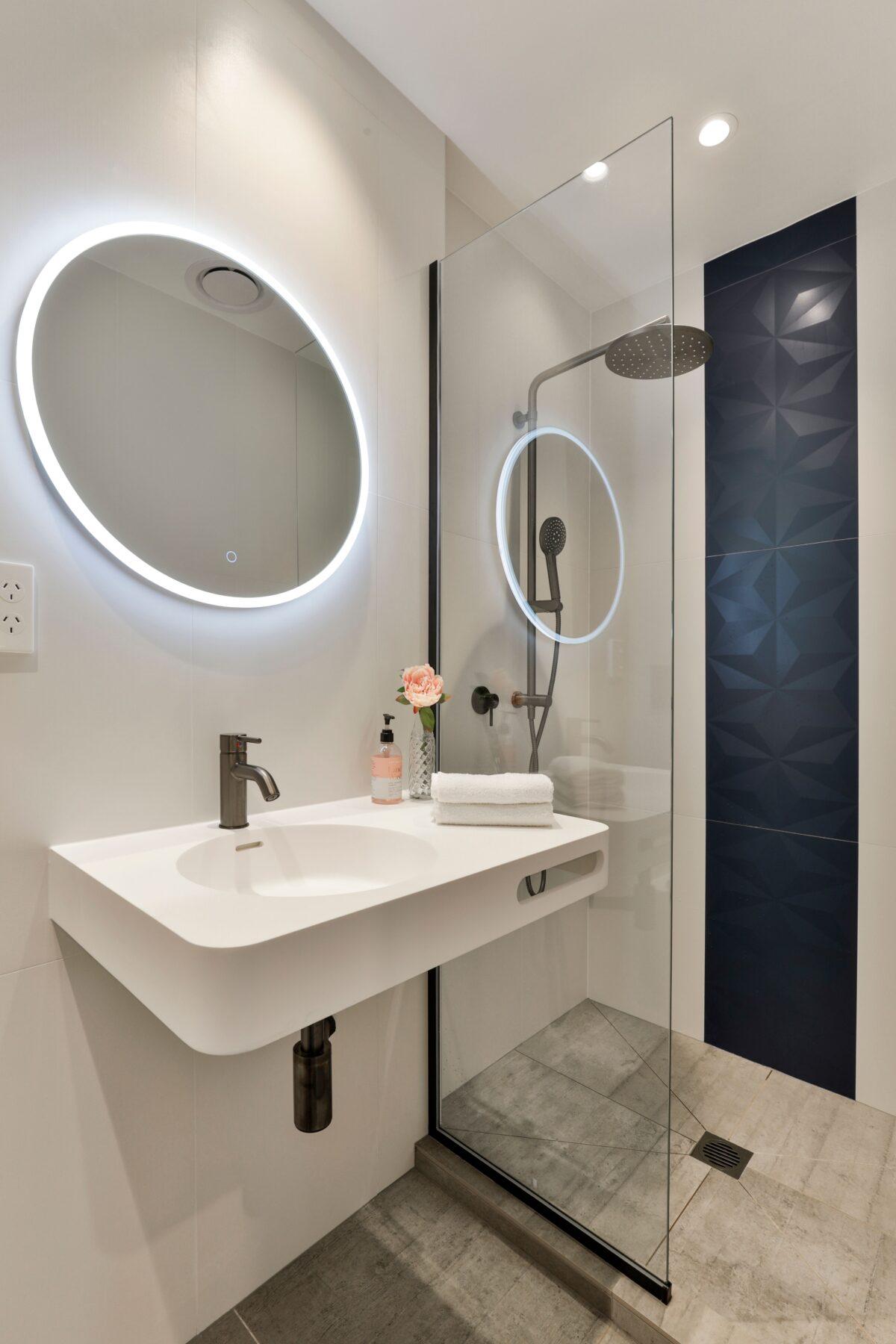 Black texture bathroom wall tiles, round LED mirror lights, simple bathroom styling