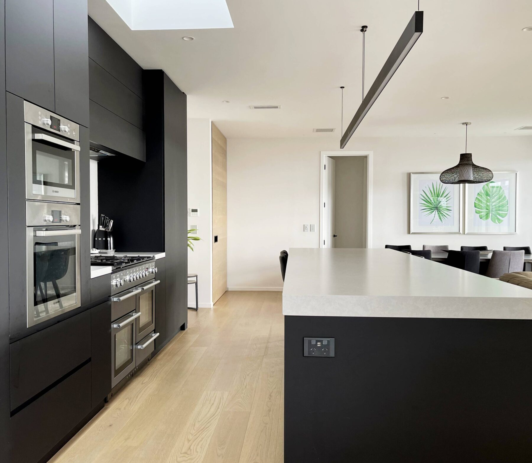 Modern contemporary kitchen with black cabinets and white stone benchtops and light wooden flooring, with black pendant lighting