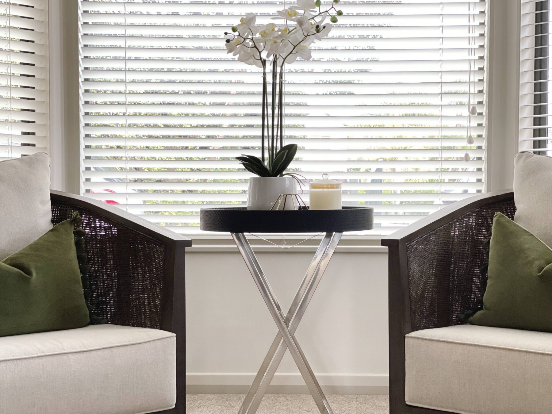 close up of dark wooden arm chairs with light linen fabric, green scatter cushions, round black side table with sliver metal legs, simple styling, white blinds, light carpet