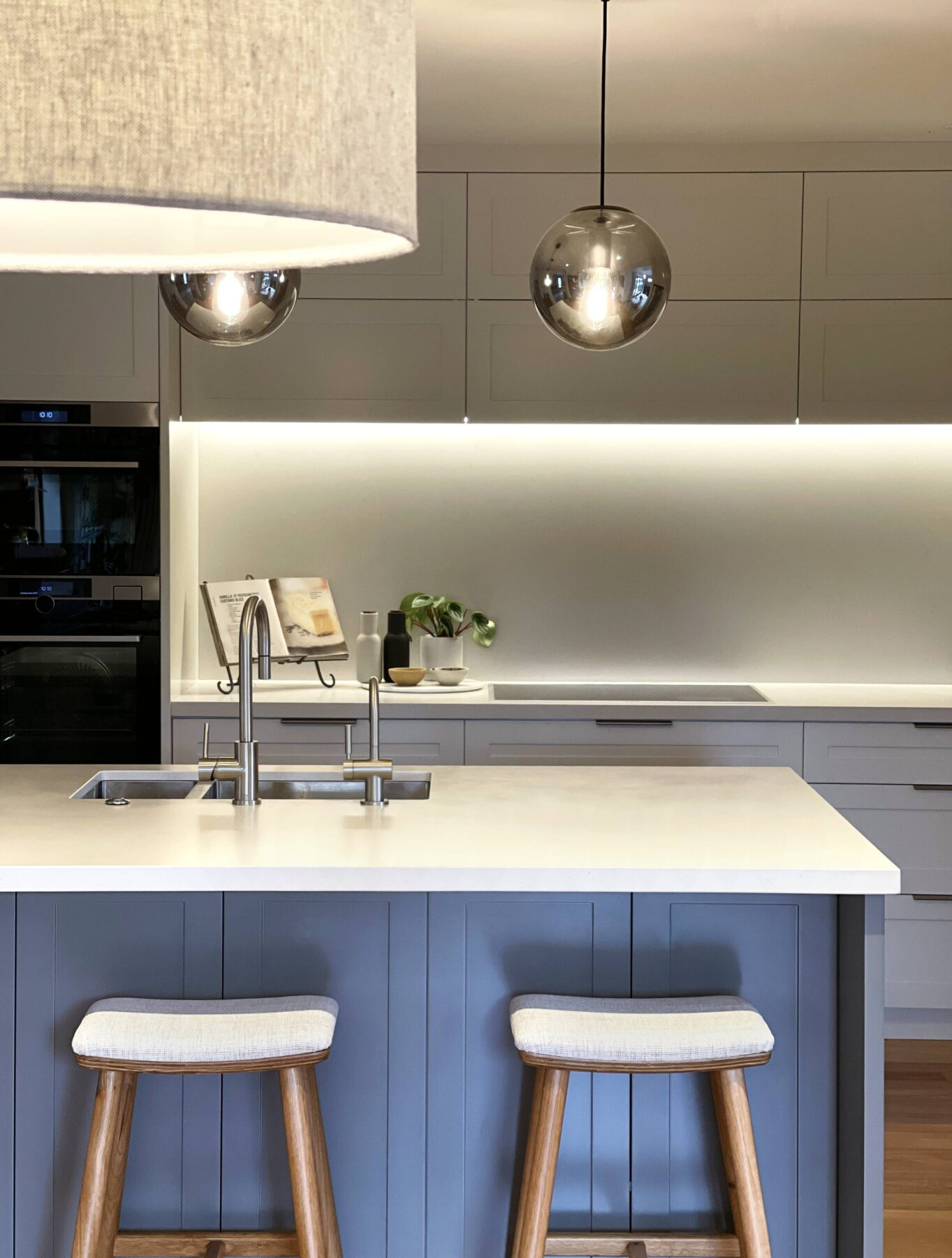 modern kitchen design white stone top, blue hamptons style panelling detailed cabinets, wooden barstools with fabric seats, sliver hanging pendent lights