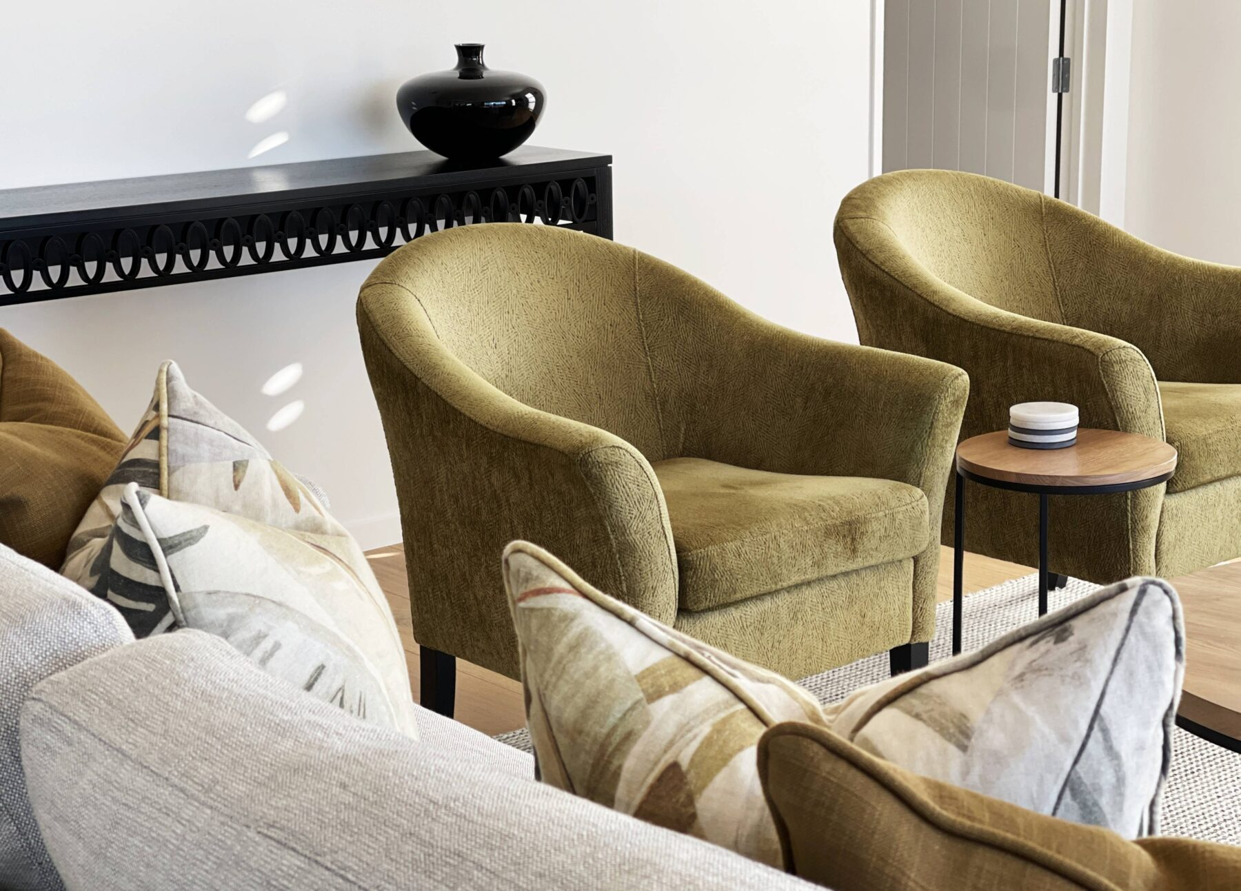close up earthy toned velvet green arm chairs, black side console with simple styling, oak round side table, decorative cushions on grey sofa
