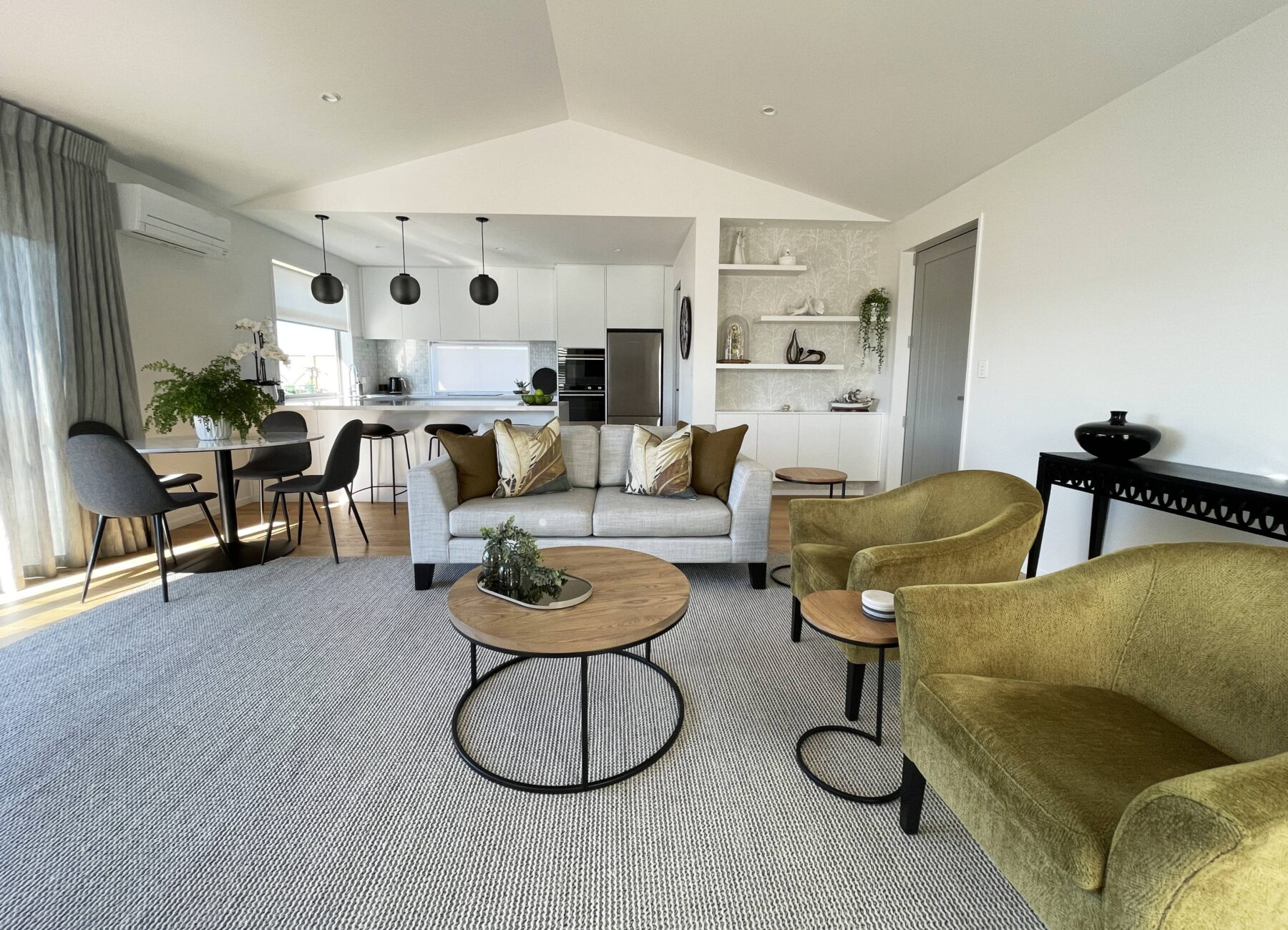 modern earthy living room, with feature green velvet arm chairs, oak wooden coffee with black metal legs, large textured rug, grey sofa with decorative cushions, simple coffee table styling, round marble dining table with black velvet chairs, black statement hanging pendant lights, custom floating shelves and wood floors
