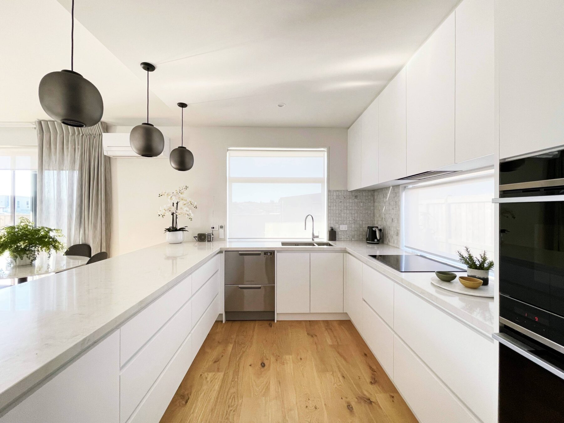 Modern white kitchen with light stone top and wooden flooring, with statement black pendant lights
