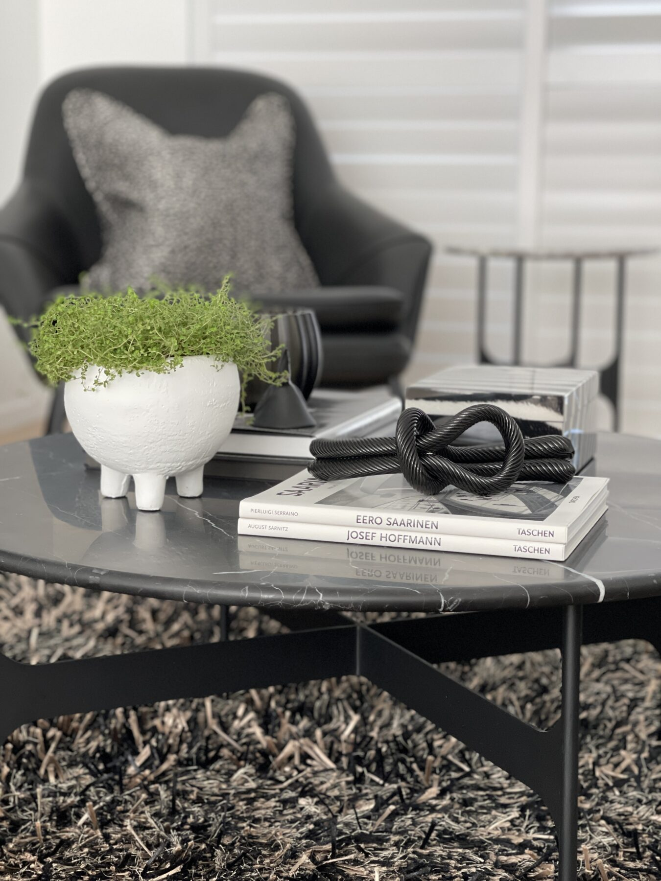 close up of black marble coffee table with monochrome table styling, black and white rug