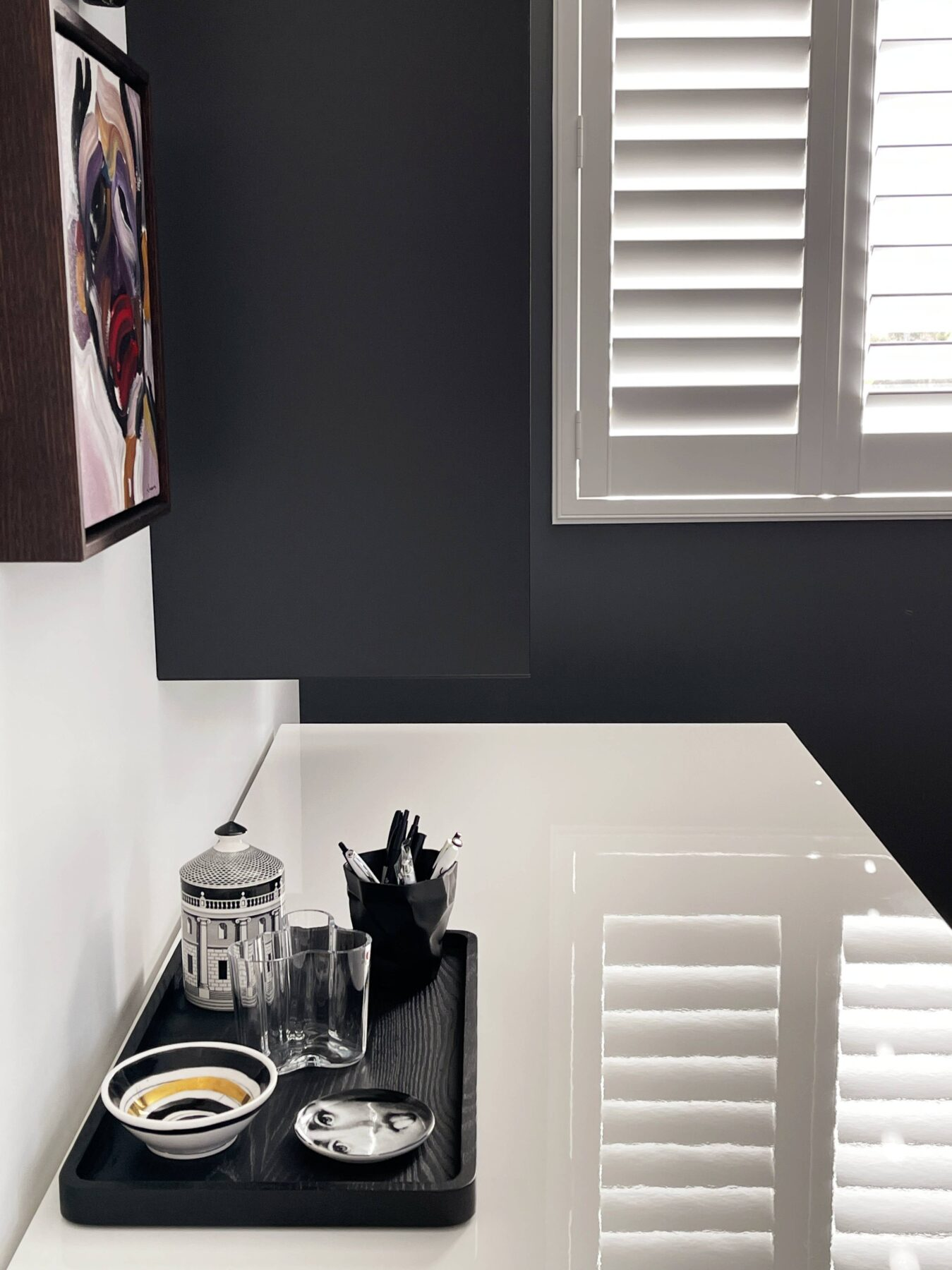 luxury monochrome office space, wall mounted hanging bookshelf, white desk with dark grey legs and simple styling, white window shutters, work from home