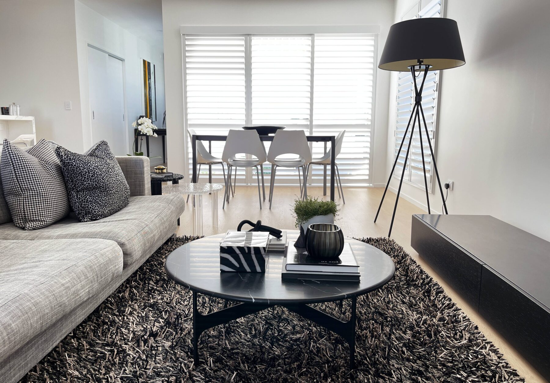 Black and white living room with black marble coffee table, black and white shaggy rug, black tv console, black standing floor lamp, white cut out dining chairs and light wood flooring, grey sofa, black and white patterned decorative cushions