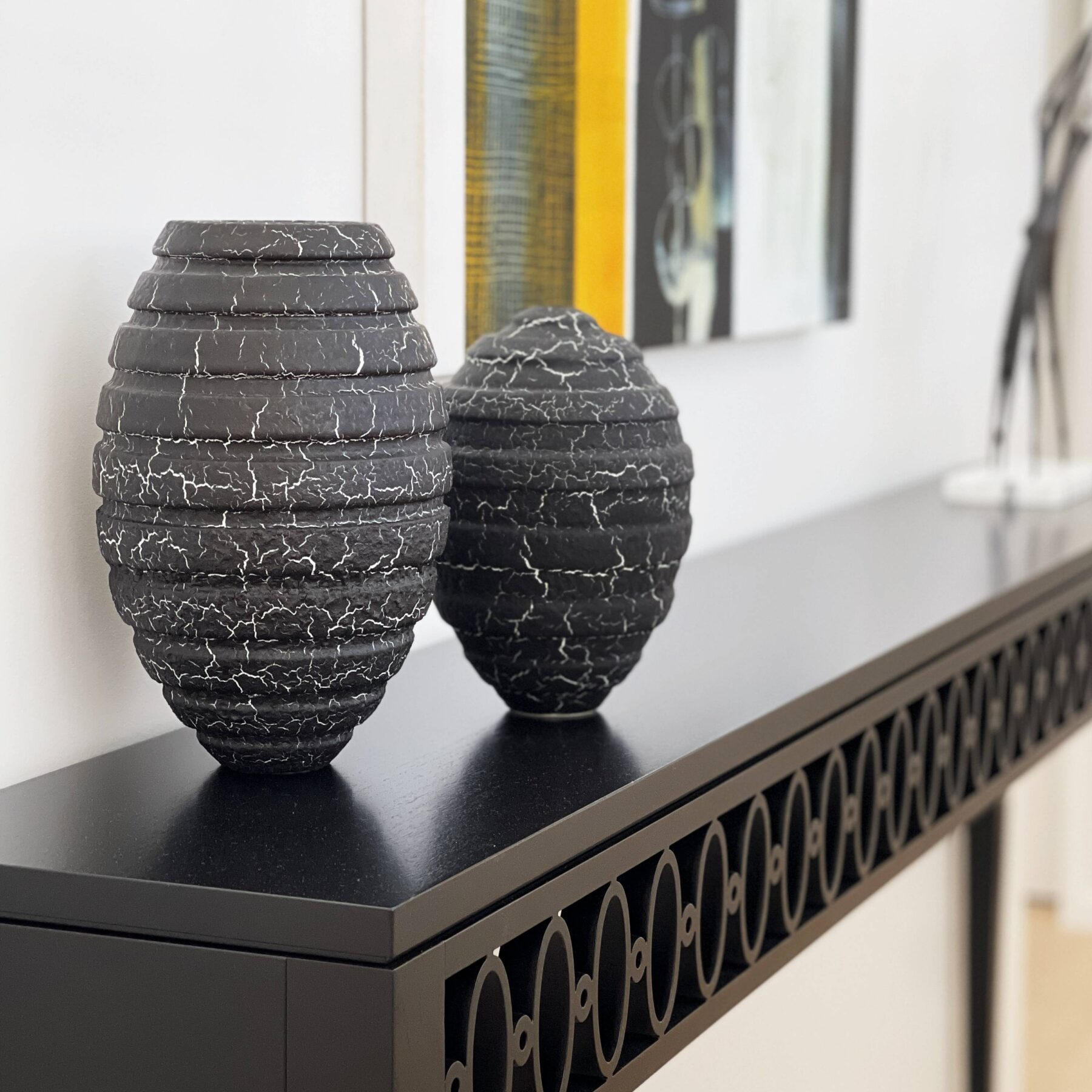 modern black custom made skinny hall console with textures vases and bright wall art