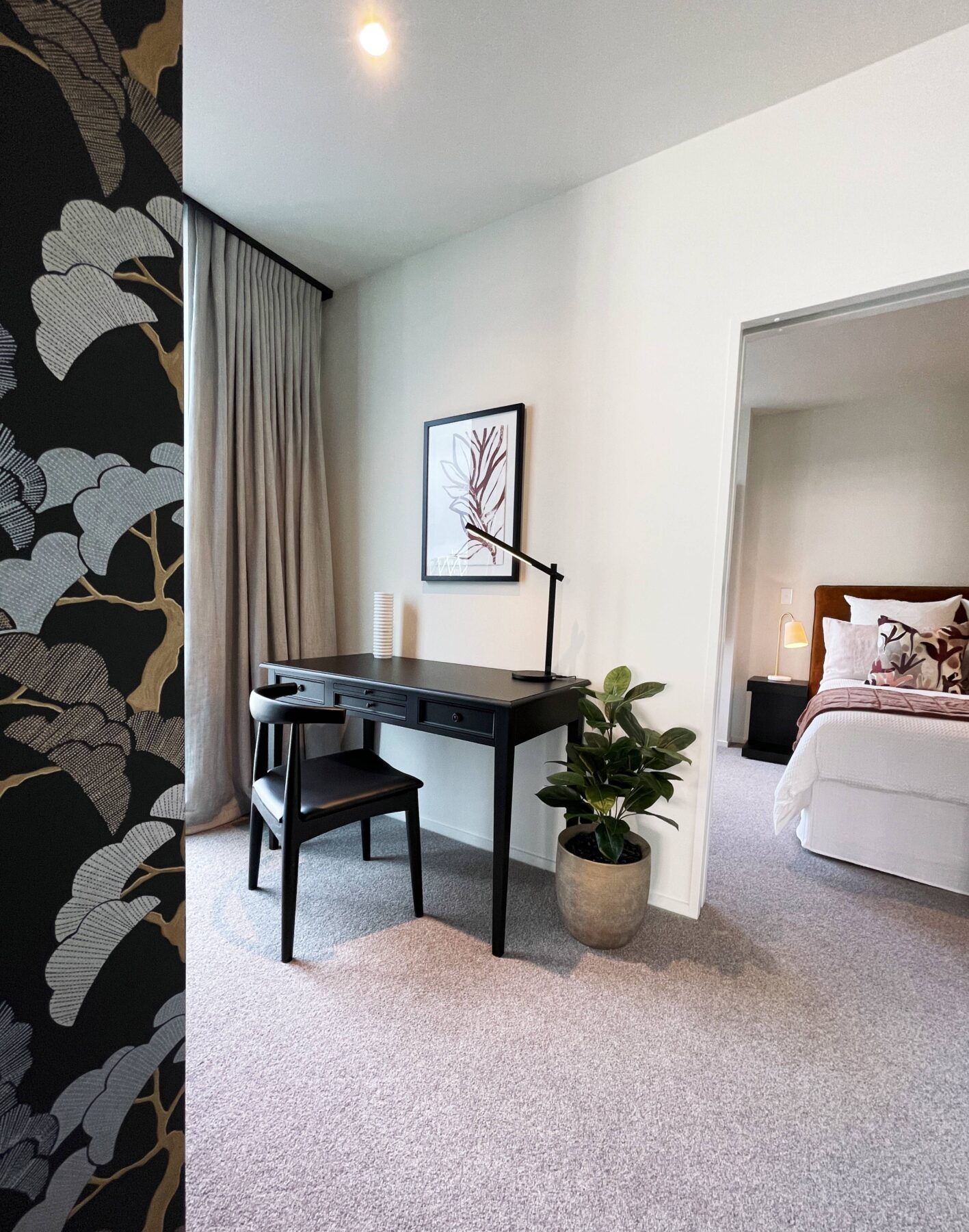 luxury apartment office space, with patterned feature wallpaper, black desk and chair, work from home space