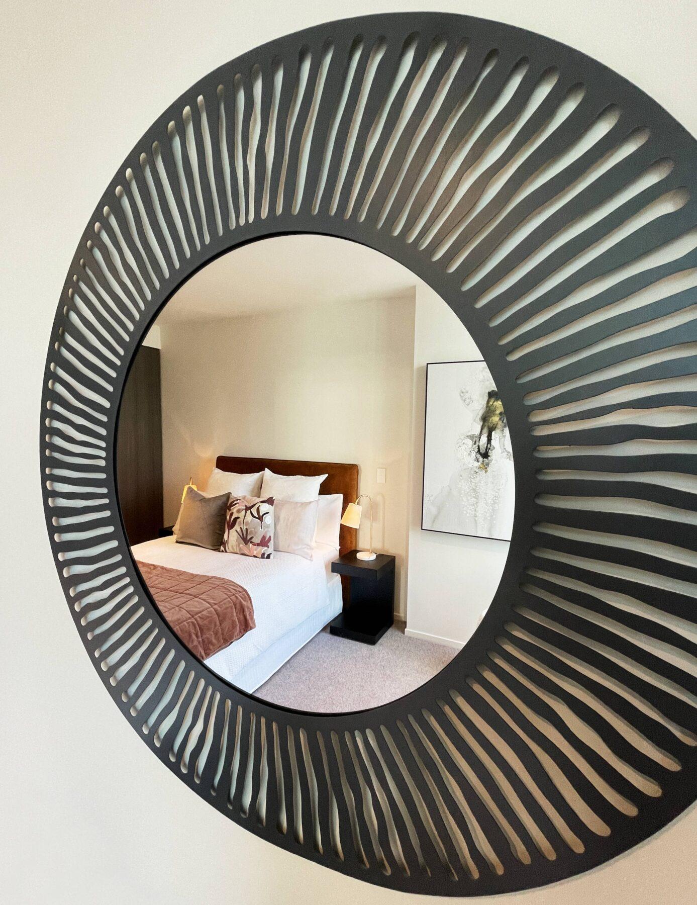 luxury bedroom with rust velvet headboard, black bedside tables, reflection in textured black metal framed round mirror