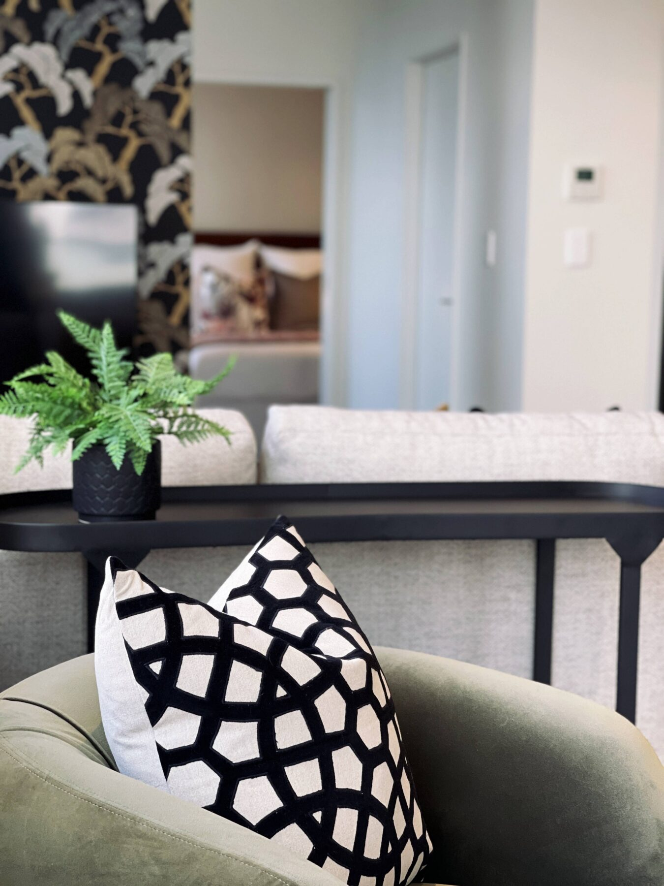 close up of luxury green velvet arm chair in small apartment lounge, with black patterned decorative cushion, black console table and feature wallpaper