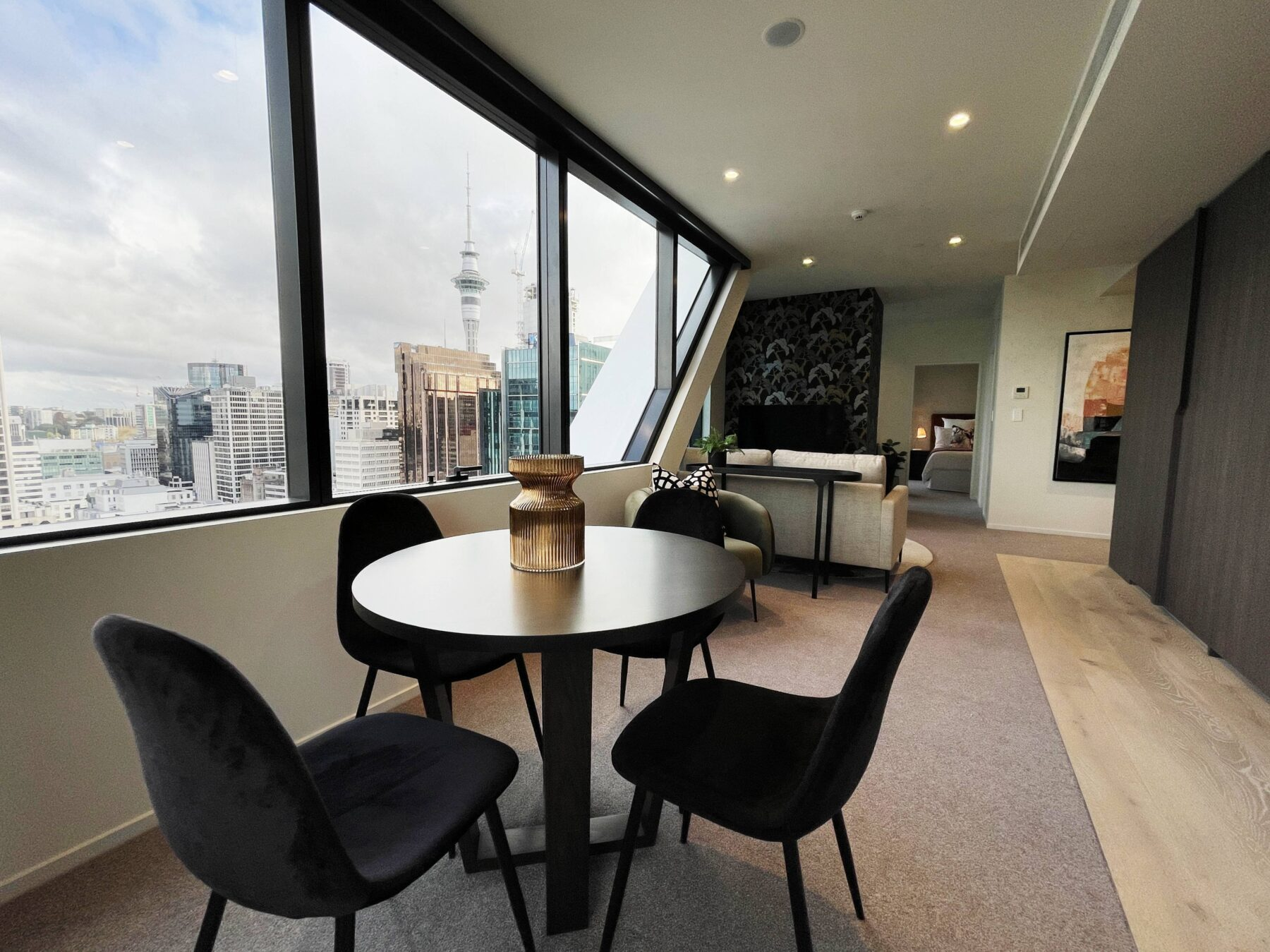 luxury city apartment living and dining space with small round dining table and black velvet chairs