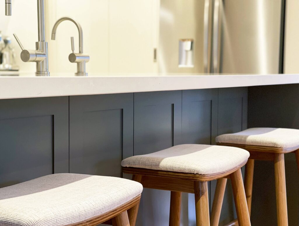 bright and modern contemporary shaker style kitchen with panelling and stone benchtop custom upholstered oak barstools