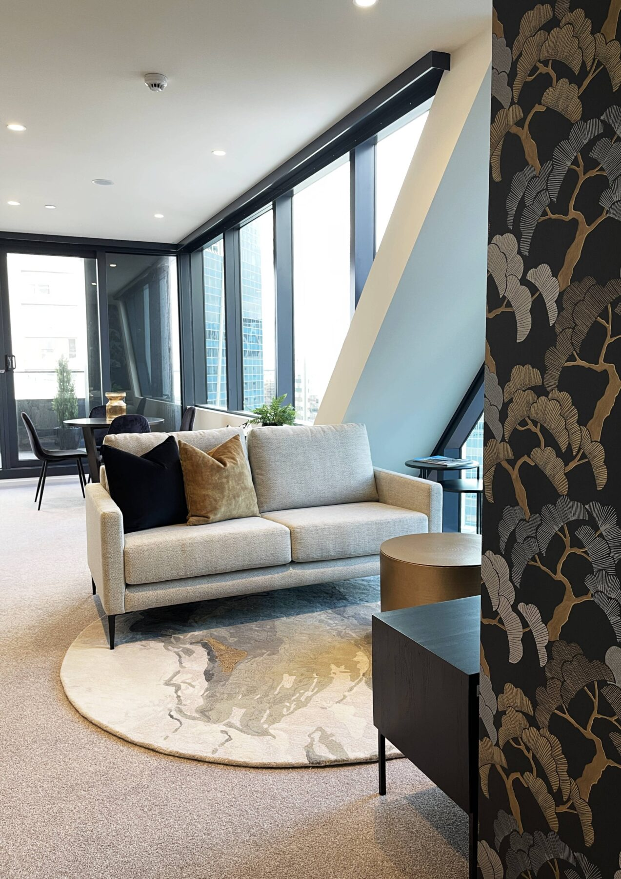 Modern contemporary luxury apartment lounge with feature black and gold wallpaper, simple styling, round rug, gold drum coffee table and auckland city views