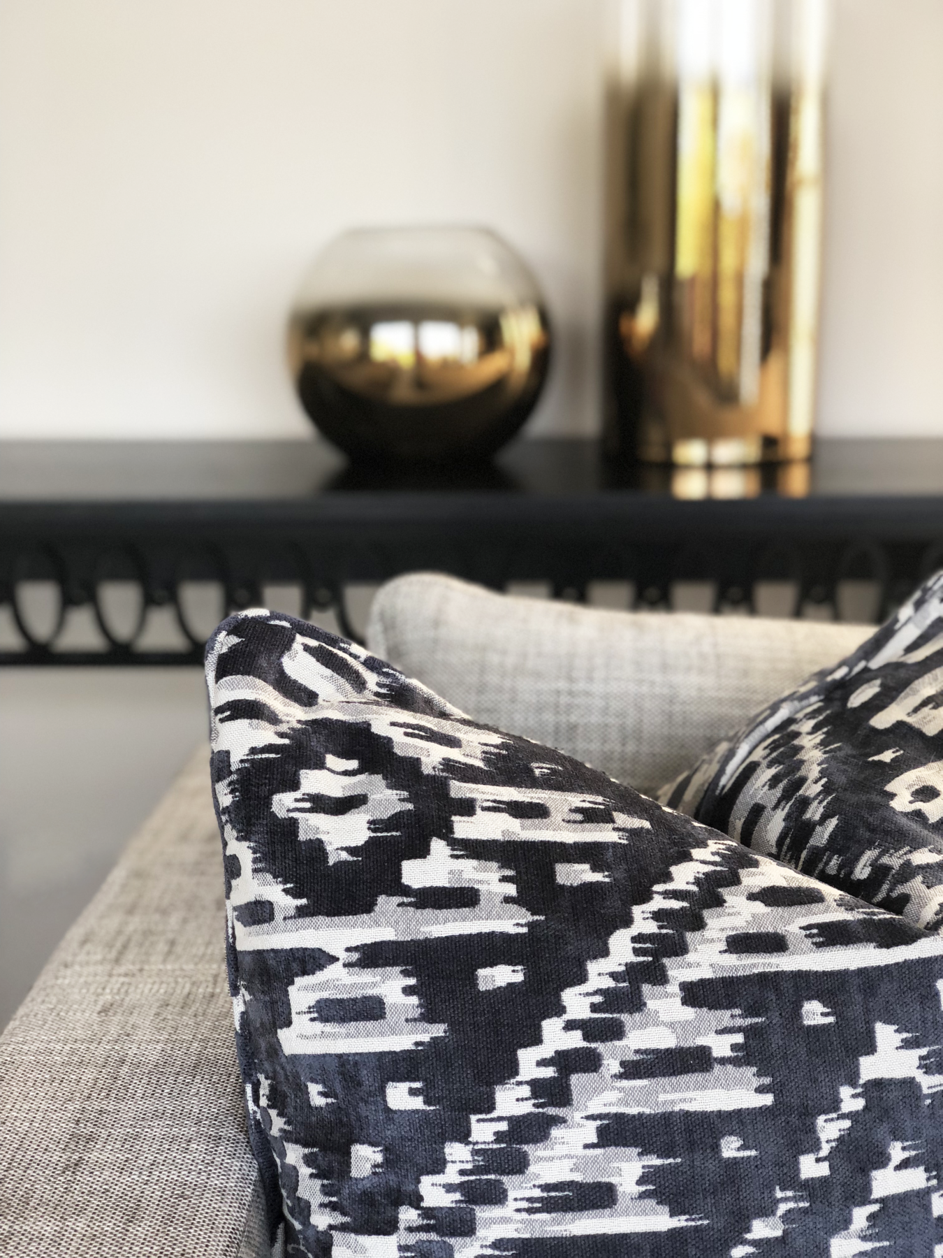 close up of designer custom cushion in black and white with gold vases on black console table