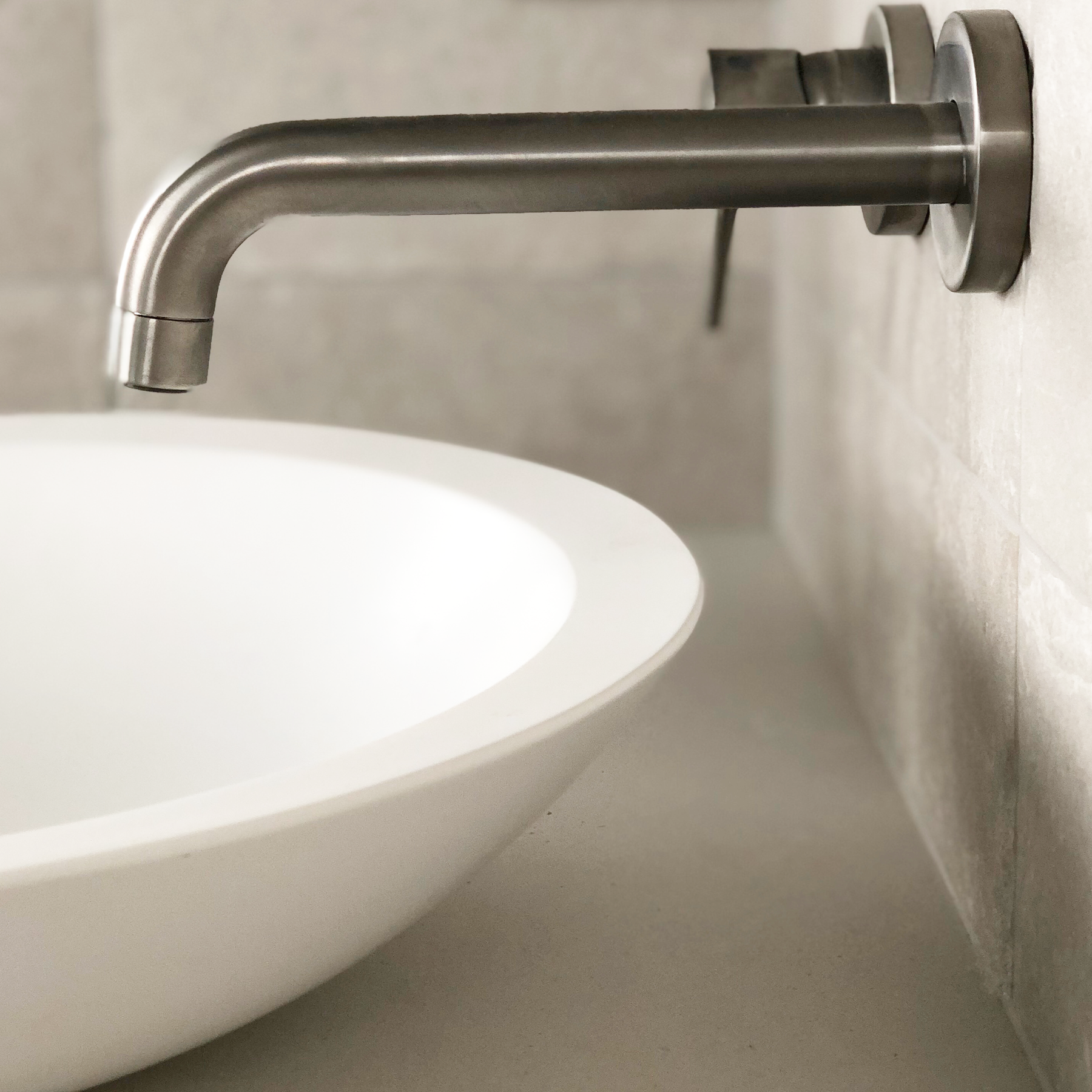close up of round bathroom sink with brushed nickel tapware