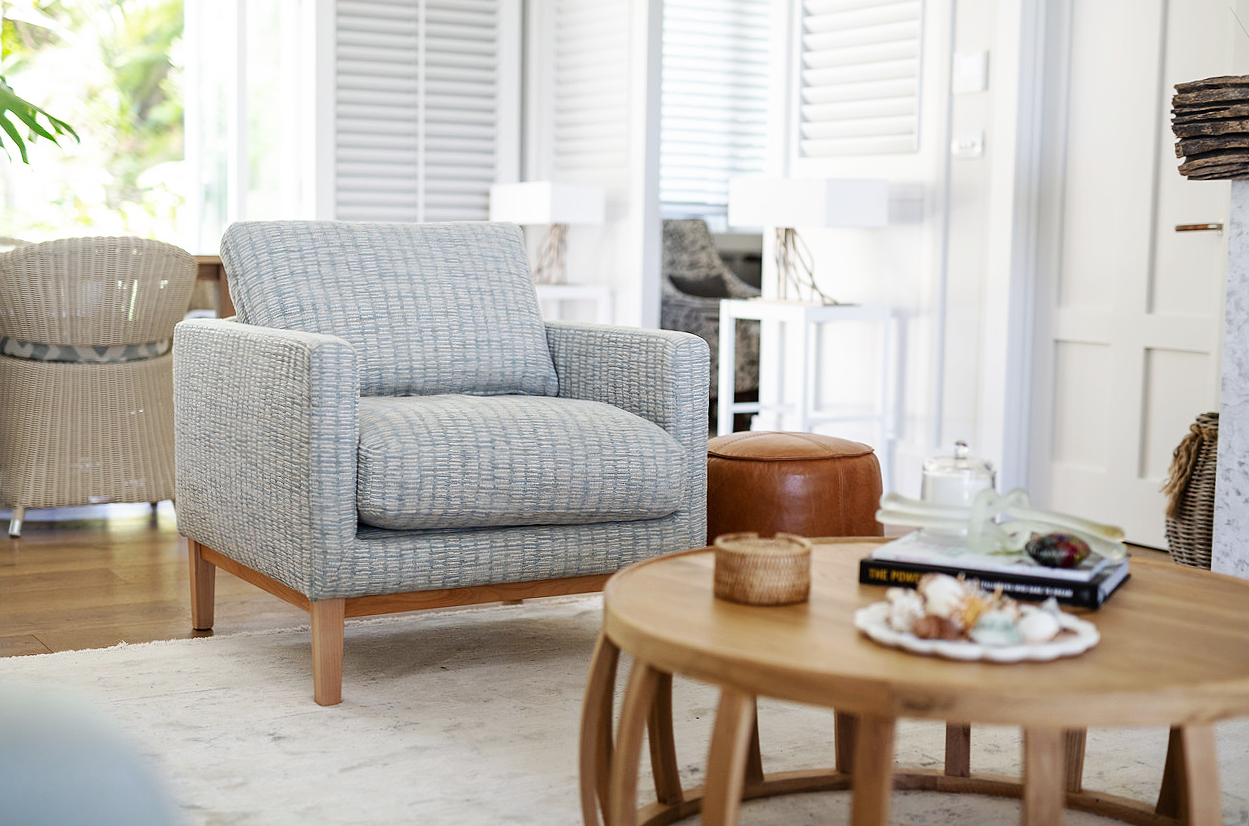 hamptons theme home with custom made textured blue armchair and round wood coffee table and white shutters