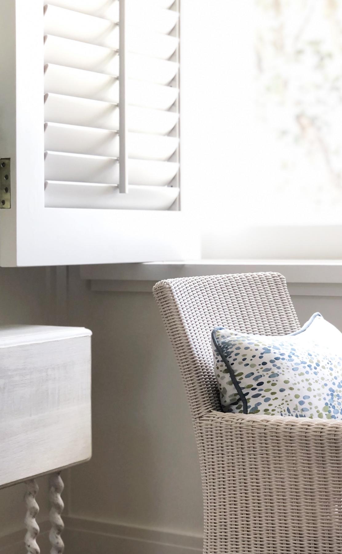 hamptons theme white rattan chair next to white window shutter