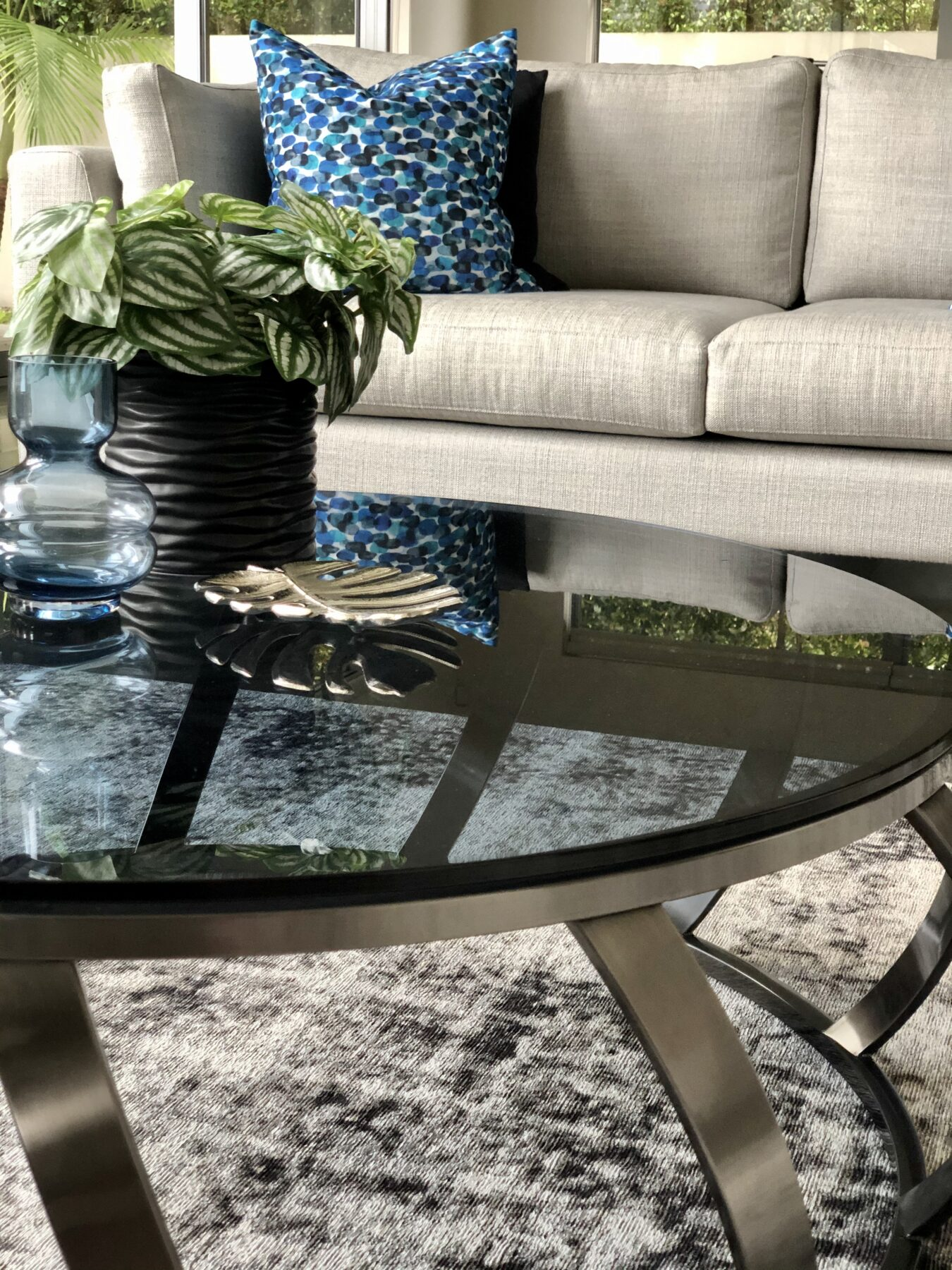 glamourous modern living room coffee table with black glass top and blue feature cushion