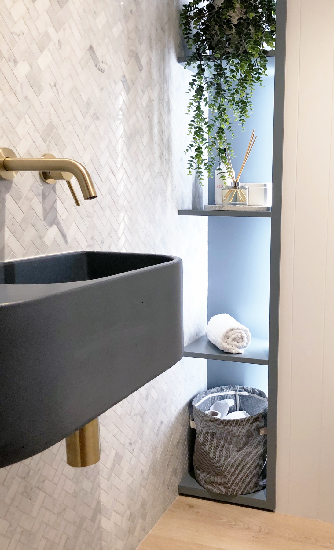 contemporary farmhouse bathroom with marble chevron tiles, brass tapware and coloured concrete sink with feature lit shelving