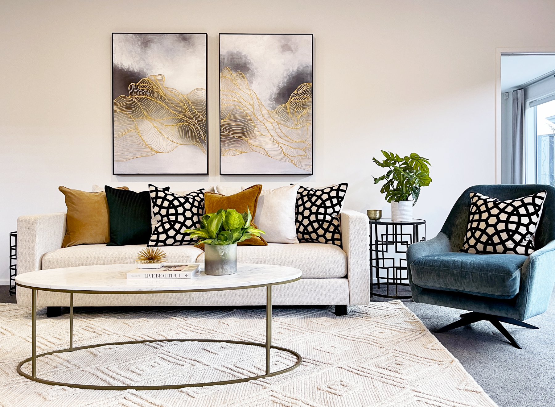 bright and fresh living room with blue black and gold highlights statement wall art and brass and marble coffee table